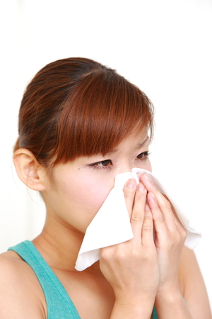 unhealthiness: young Japanese woman sneezing with allergy or cold Stock Photo
