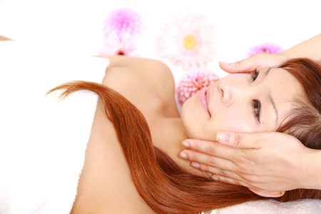 young Japanese woman getting a face massage  photo