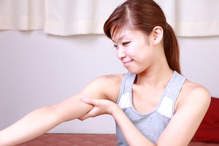 young woman doing self arm massage Stock Photo