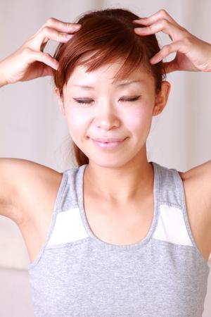 セルフ マッサージを行う若い女性 写真素材