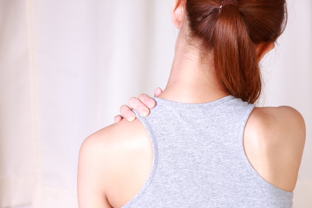 self care: young woman doing self shoulder massage Stock Photo