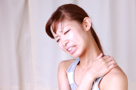 stiff: young Japanese woman suffers from stiff neck