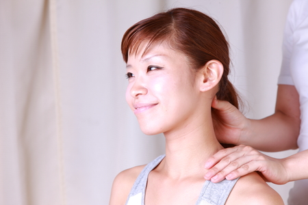young Japanese woman getting a neck massage