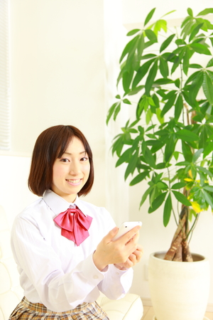 female high-school student with smart phone photo