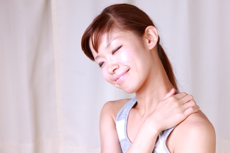 young woman doing self shoulder massage Stock Photo