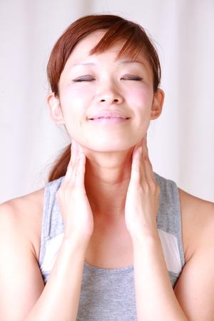자기 목 마사지를하는 젊은 여자