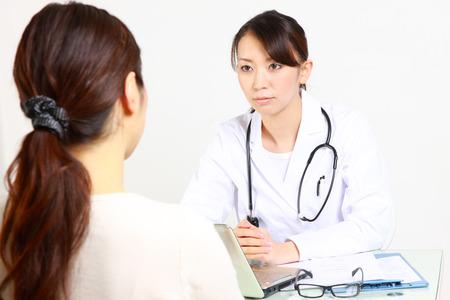 conversa: M�dico femenina japonesa habla con su paciente Foto de archivo