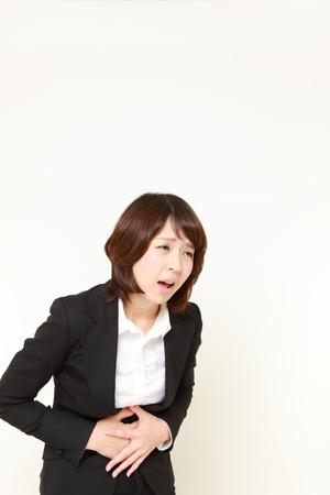 gastroenteritis: businesswoman suffers from stomachache Stock Photo