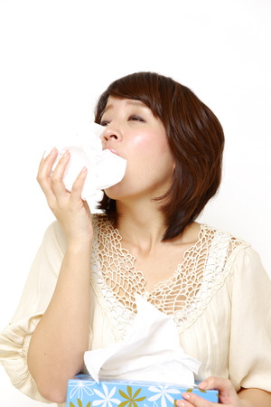 woman with a allergy sneezing into tissue photo