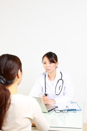 conversa: Mujer m�dico japon�s habla con su paciente Foto de archivo