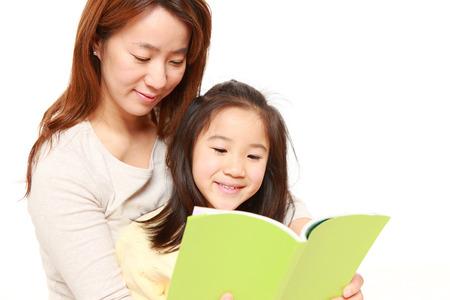 mom daughter: Madre japonesa leyendo un libro a su hija Foto de archivo