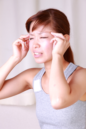 young Japanese woman suffers from head ache