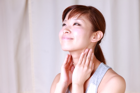 young Japanese woman doing a lymph node massage photo