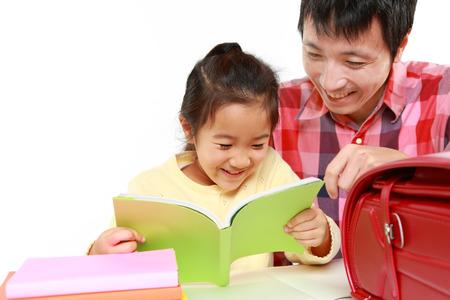 niños estudiando: padre ayudando a su hija hacer la tarea Foto de archivo