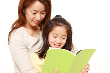 apanese mother reading a book to her daughter