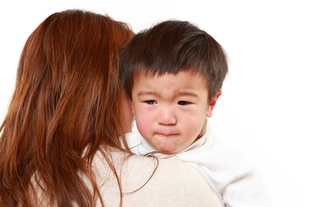 sad cute baby: crying Japanese little boy who is being held by her mother