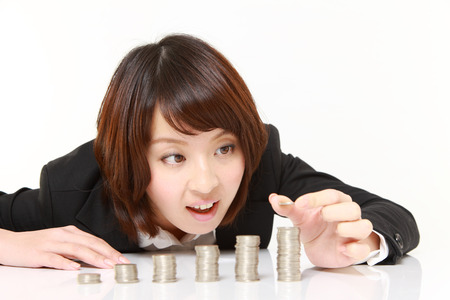 Businesswoman Put Coins To Stack Of Coins photo