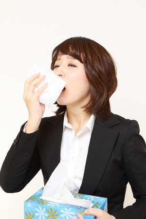 businesswoman with a allergy sneezing into tissue photo