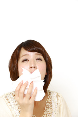 young woman with a allergy sneezing into tissue photo