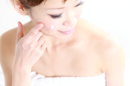 young Japanese woman applying cream on her face Banco de Imagens