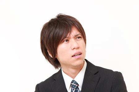 worries: young Japanese businessman worries about something Stock Photo