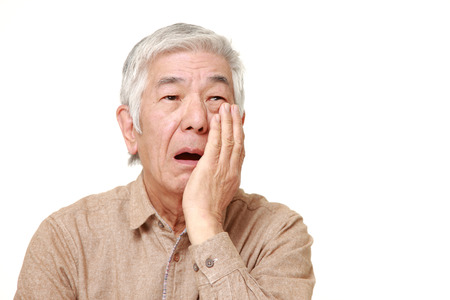 suffers: senior Japanese man suffers from toothache