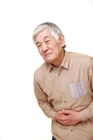 gastroenteritis: senior Japanese man suffers from stomachache Stock Photo