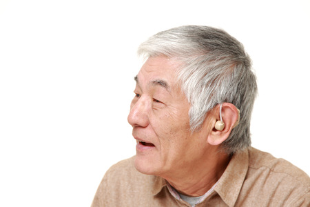 deafness: senior Japanese man with hearing aid