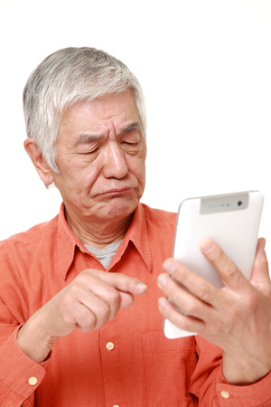 senior Japanese man using tablet computer looking confused Stock Photo