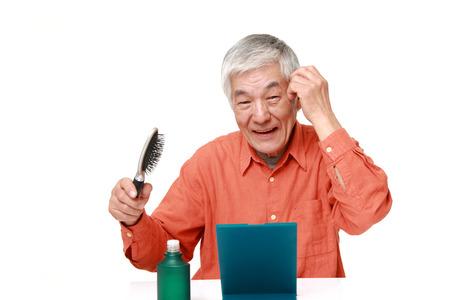育毛剤を使用して年配の日本人男性 写真素材