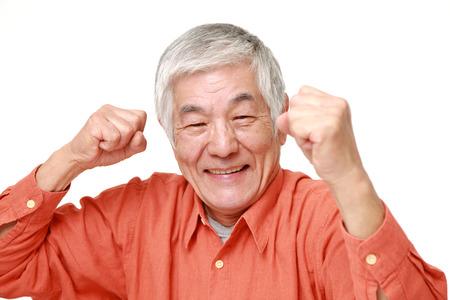 勝利のポーズでシニアの日本人男性 写真素材