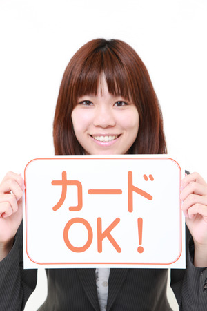 net trade: businesswoman holding a message board with the phrase credit card accepted in Japanese