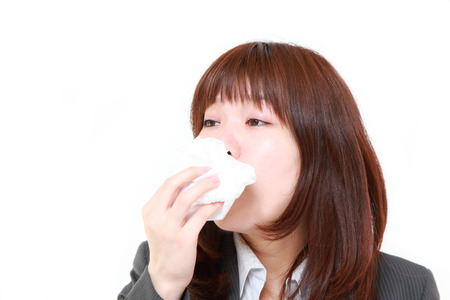 sneezing: businesswoman with an allergy sneezing into tissue