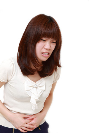stomachache woman: young Japanese woman suffers from stomachache Stock Photo