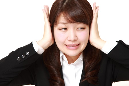 wry: Young Japanese businesswoman suffers from noise Stock Photo