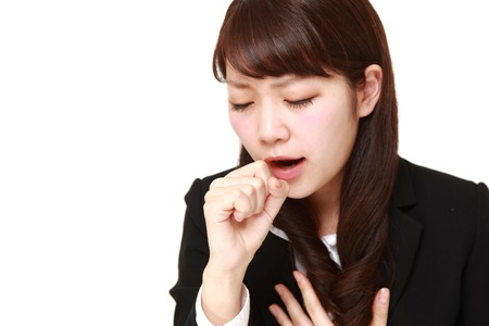 coughing: young Japanese businesswoman coughing