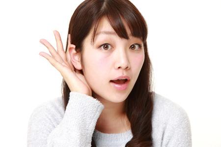 密接に聞く耳の後ろに手を持つ若い女性