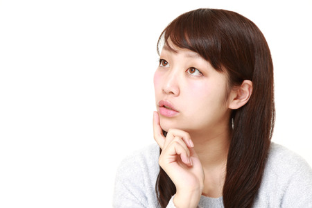 young Japanese woman thinks about something