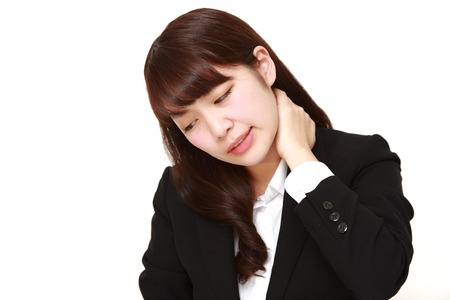 suffers: portrait of Japanese businesswoman suffers from neck ache