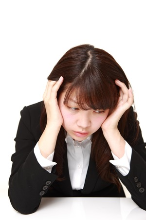 worries: portrait of young Japanese businesswoman worries Stock Photo