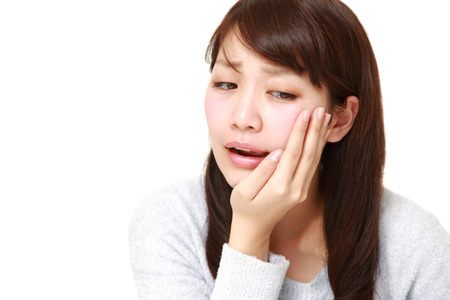 portrait of a young Japanese woman suffers from toothache