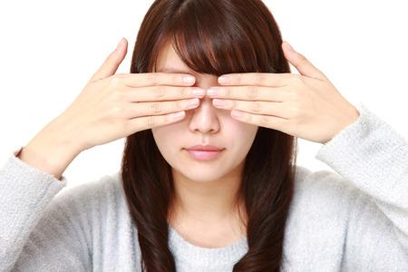 女性の手で彼女の顔を覆っています。