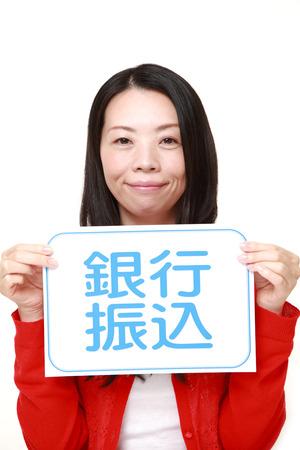 bank overschrijving: vrouw die een message board met de zin overschrijving in KANJI Stockfoto