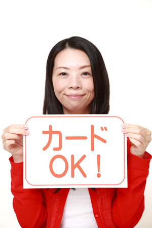 accepted: woman holding a message board with the phrase CREDIT CARD ACCEPTED in Japanese Stock Photo