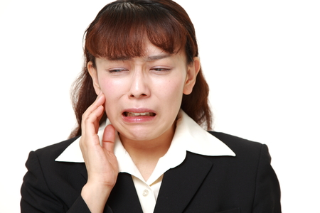 suffers: asian businesswoman suffers from toothache Stock Photo