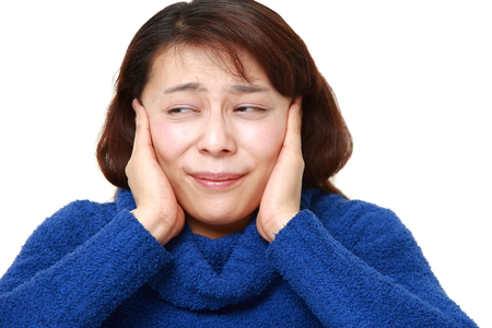 unattractive: asian woman suffers from noise