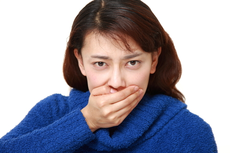 unattractive: asian woman covering with hands her mouth