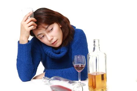 tomando alcohol: Mujer asi�tica en la depresi�n est� bebiendo alcohol