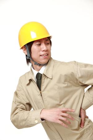 腰痛に苦しんでいる建設労働者 写真素材