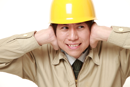suffers: Young Japanese construction worker suffers from noise